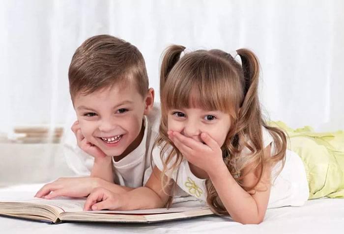 Дети читают книжку и смеются