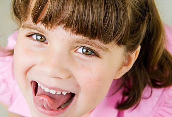 Девочка делает упражнение для языка