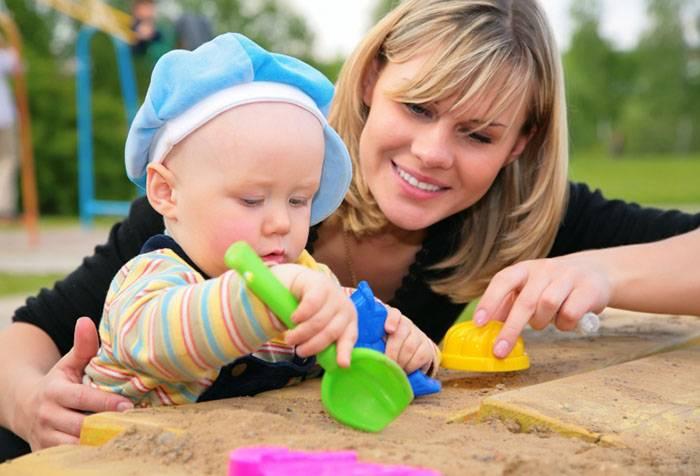 Мама играет с ребенком в песочнице