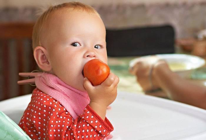 Ребенок грызет помидор