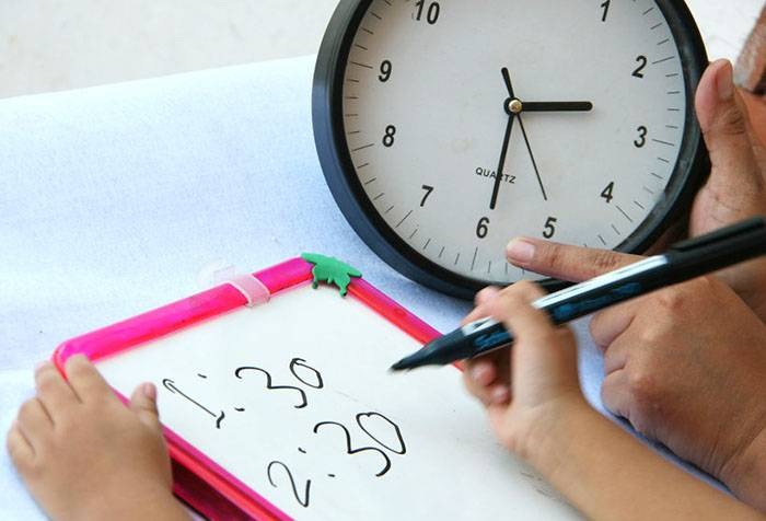 Ребенок учится определять часы и минуты
