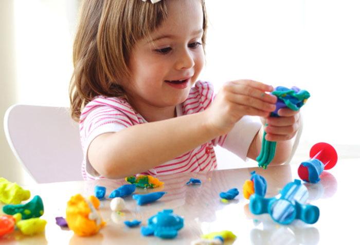 Трехлетняя девочка лепит из пластилина