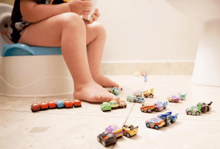 Ребенок сидит на горшке и играет с машинками