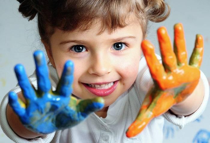 Четырехлетняя девочка играет с красками
