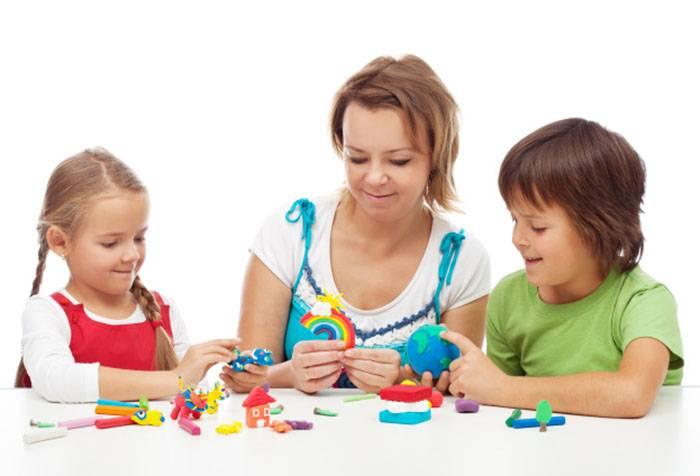 Женщина лепит из пластилина с детьми