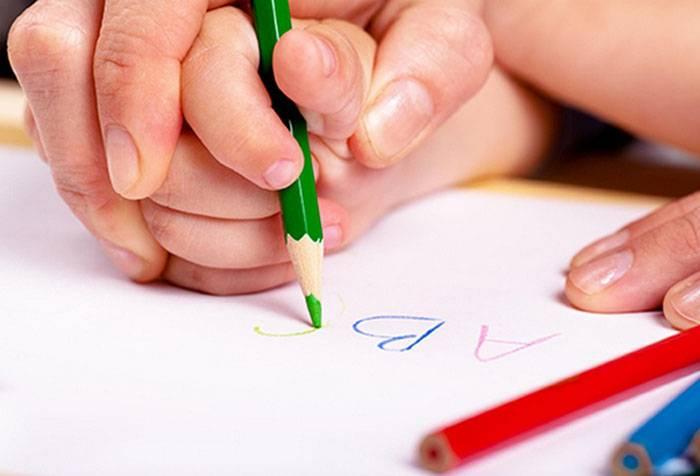 Взрослый учит ребенка писать карандашом