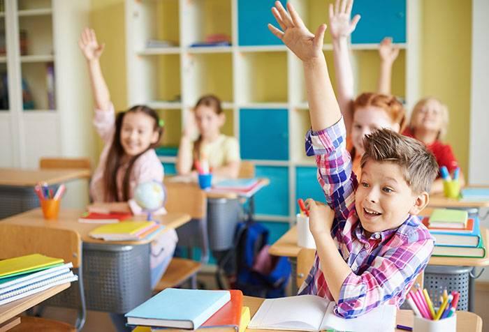 Дети тянут руки на уроке