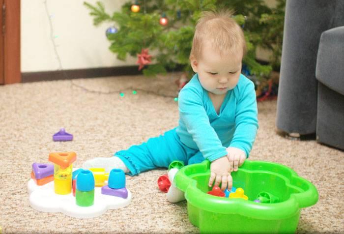 Ребенок складывает игрушки в тазик