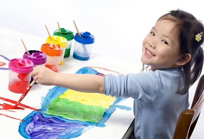 Девочка-левша рисует красками