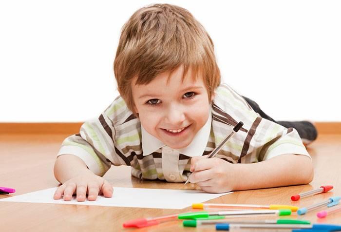 Мальчик рисует левой рукой