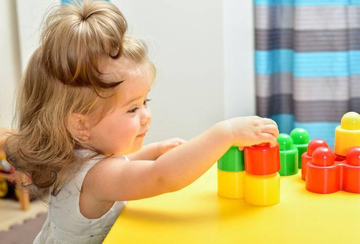 Девочка играет с детским конструктором