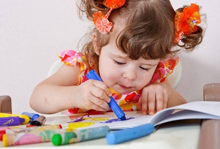 Двухлетняя девочка рисует