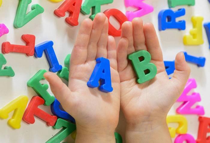 Ребенок держит буквы английского алфавита