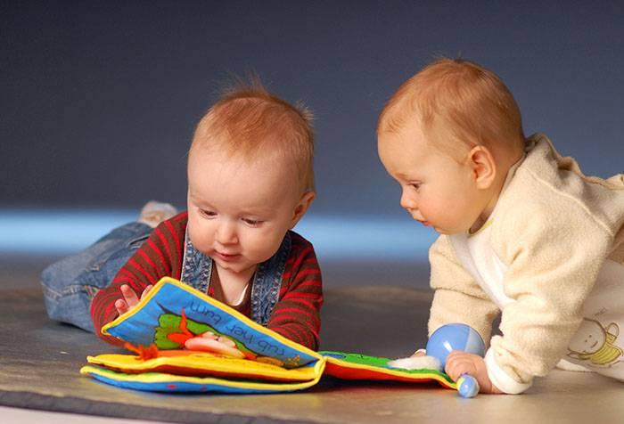 Маленькие дети с сенсорной книжкой