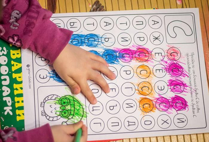 Ребенок закрашивает буквы