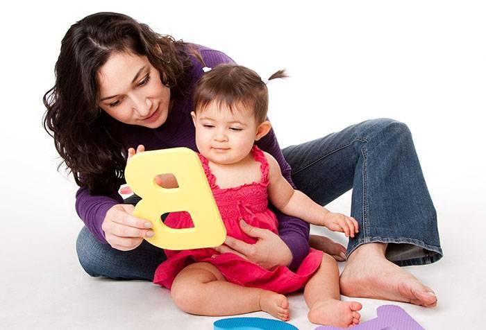 Мама показывает буквы маленькой дочке