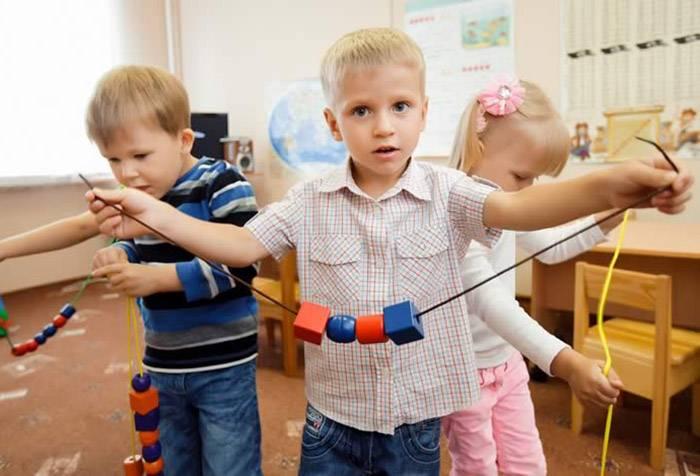 Дети нанизывают фигуры на шнурки