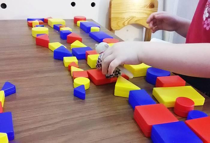 Ребенок собирает цепочку из блоков Дьенеша