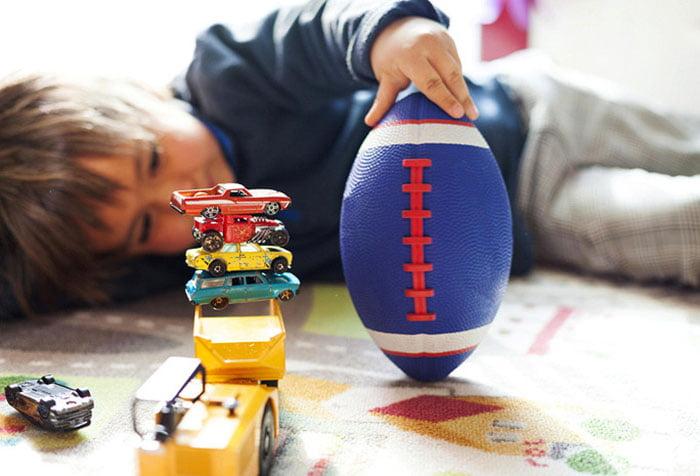 Мальчик играет лежа на ковре