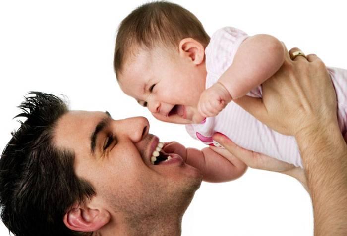 Папа поднимает смеющегося малыша