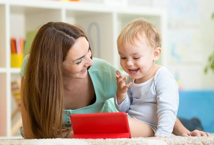 Мама с ребенком смотрят мультфильм на планшете