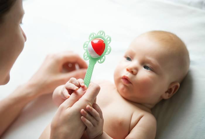 Малыш берет погремушку из рук мамы
