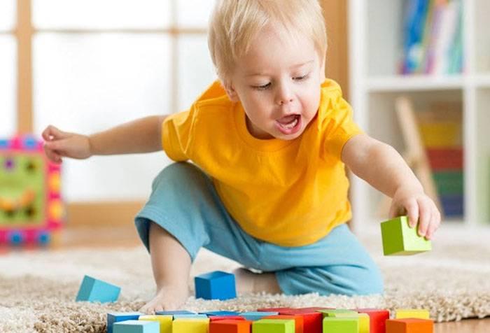 Двухлетний ребенок играет с кубиками