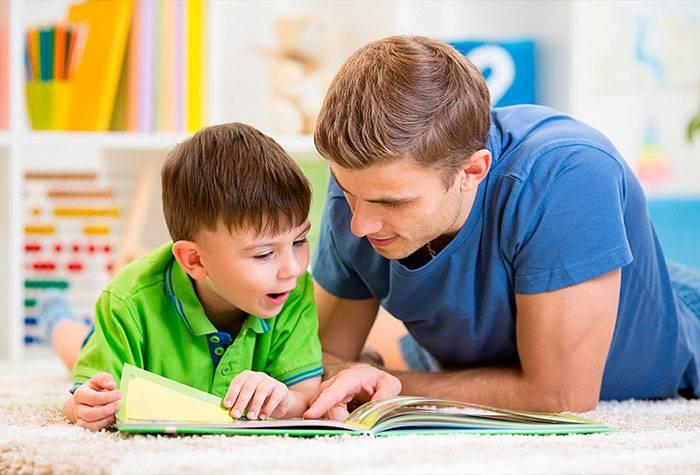 Шестилетний ребенок с папой рассматривают книжку
