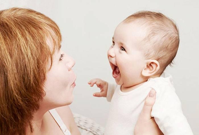 Малыш смеется на руках у мамы