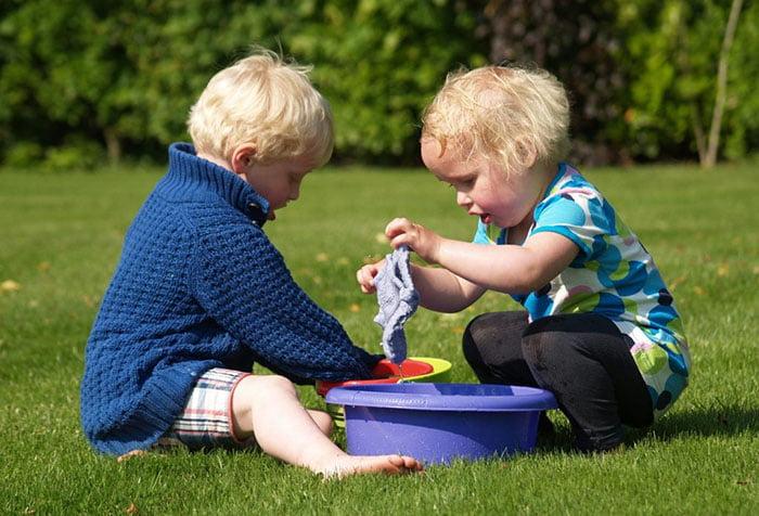 Малыши на газоне играют в стирку