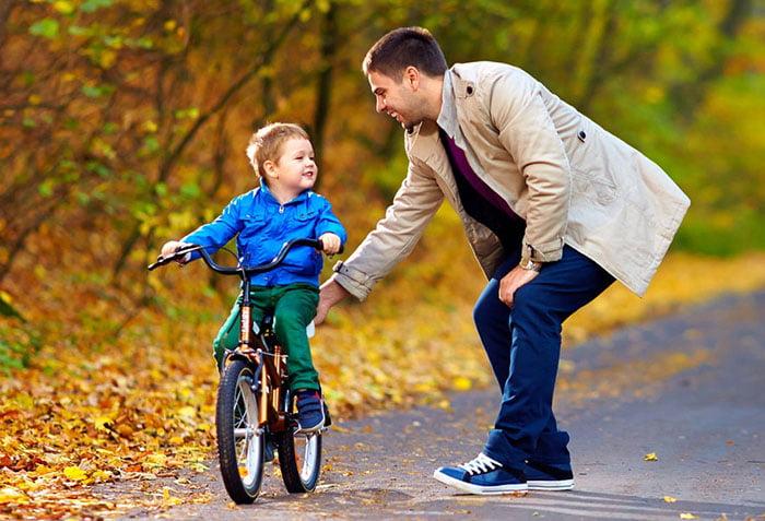 Папа учит сына кататься на велосипеде