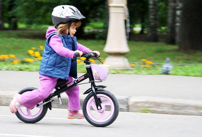 Девочка на маленьком двухколесном велосипеде