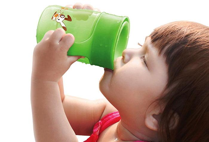 Ребенок пьет из детской кружки