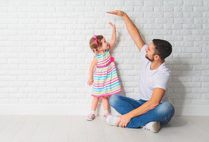 Мужчина измеряет рост двухлетней девочки