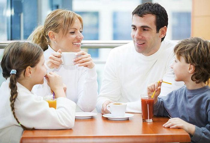 Родители с детьми общаются за столом