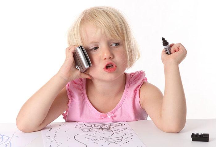 Девочка рисует и разговаривает по мобильному