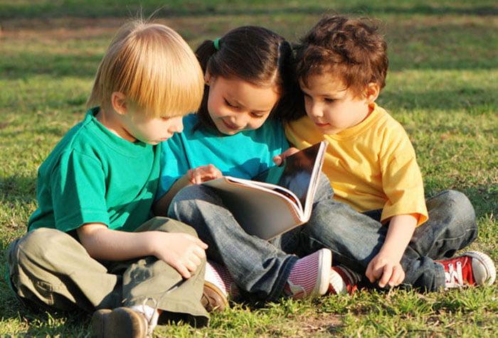 Дети читают книжку на улице
