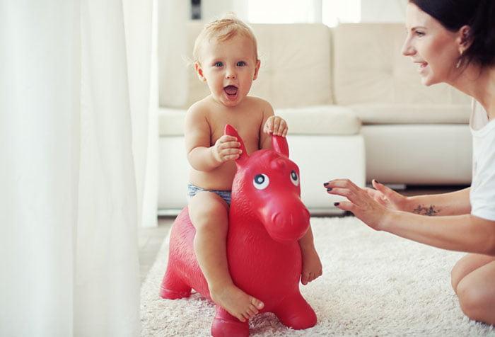 Маленький ребенок на игрушечной лошадке