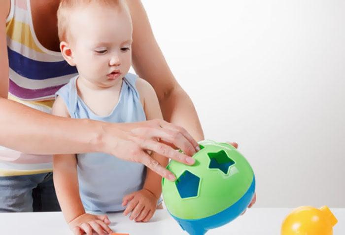 Мама показывает ребенку развивающую игрушку