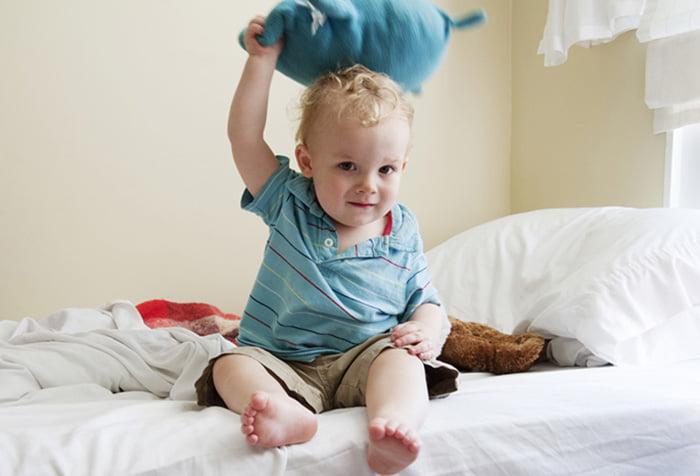 Малыш играет на кровати