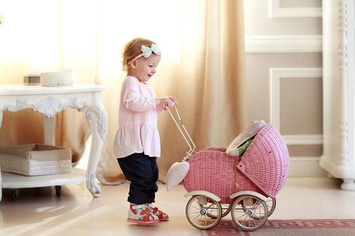 Маленькая девочка с игрушечной коляской