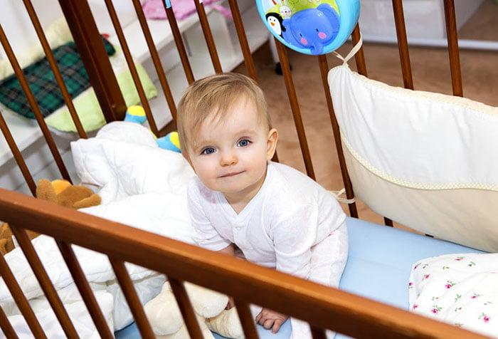 Малыш сидит в кроватке