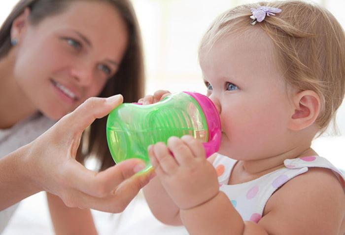 Мама учит дочку пить из поильника