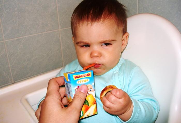 Малыш пьет сок через трубочку