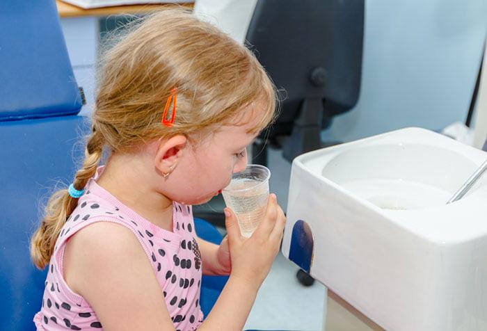 Девочка учится полоскать горло