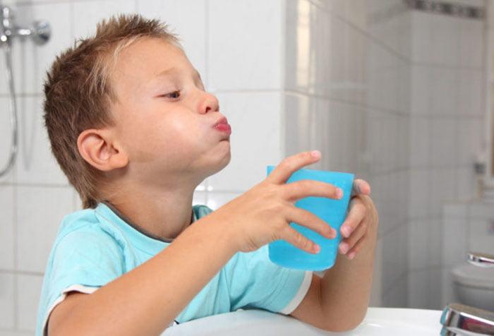 Мальчик полоскает рот и горло