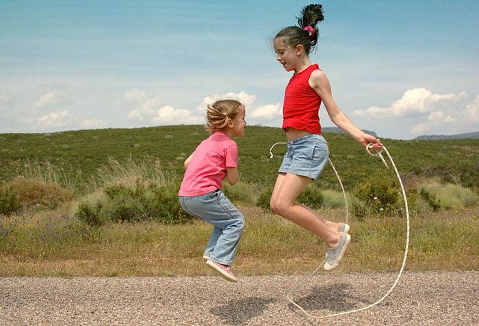 Девочки вдвоем прыгают через скакалку