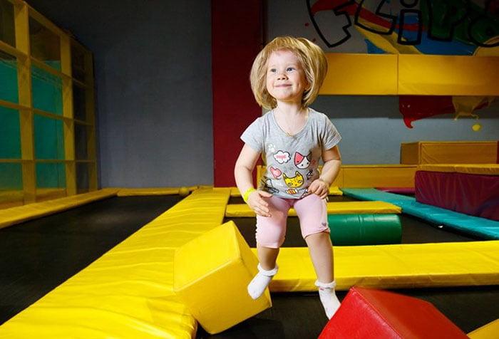 Маленькая девочка прыгает на батуте