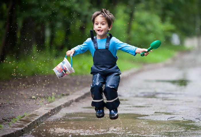 Ребенок прыгает по лужам