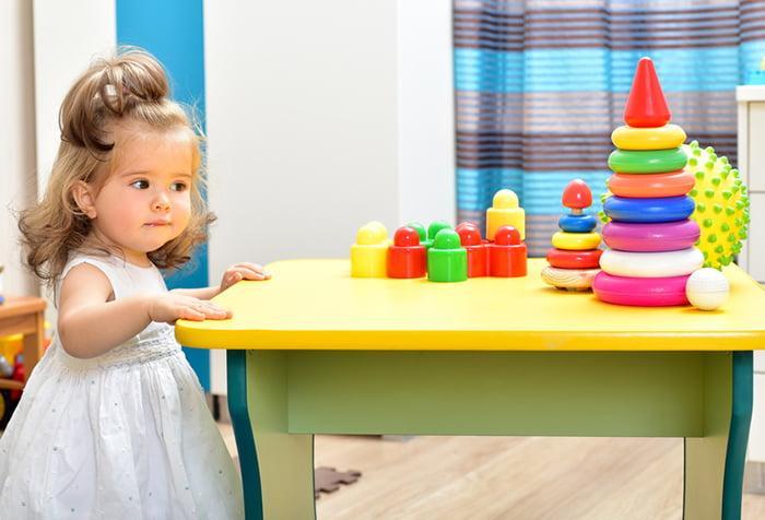 Девочка у стола с развивающими игрушками